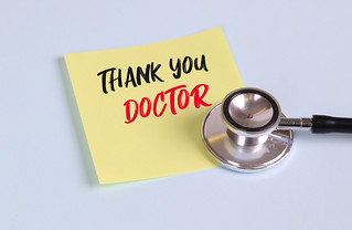 Yellow sticky note paper with stethoscope, with Thank You Doctor message | by focusonmore.com