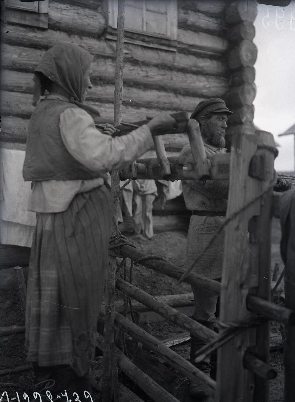 Крестьяне укладывают на сани овсяные бабки