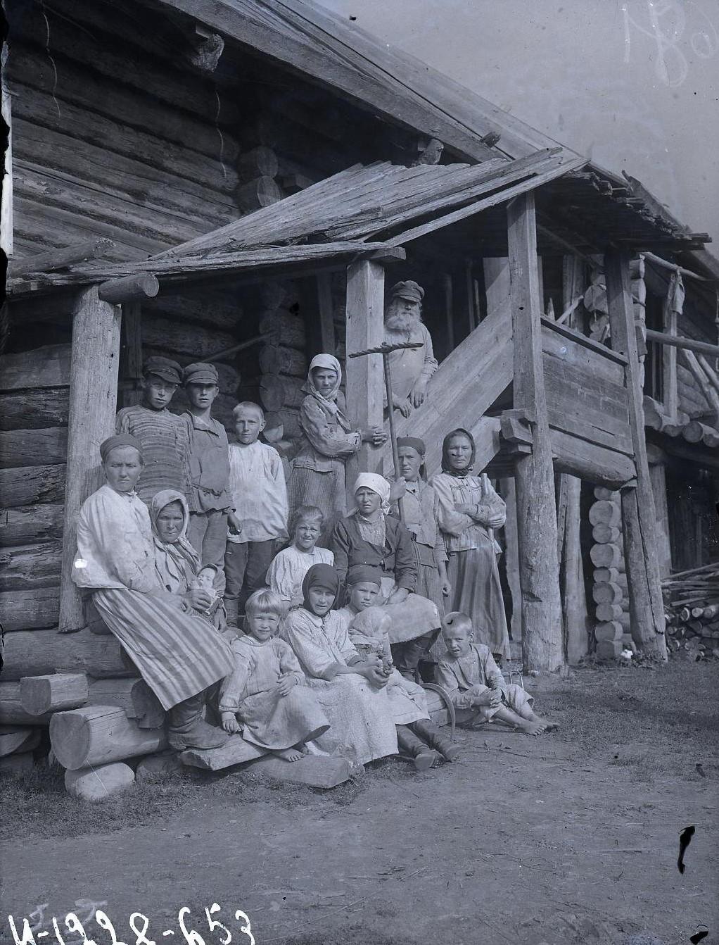 Группа крестьян с детьми на крыльце старой избы