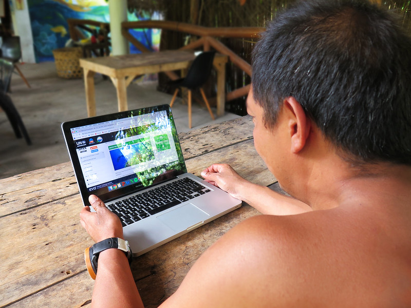 Photo of a Filipino dive guide sitting at his laptop and reading the Green Fins Dive Guidie e-Course