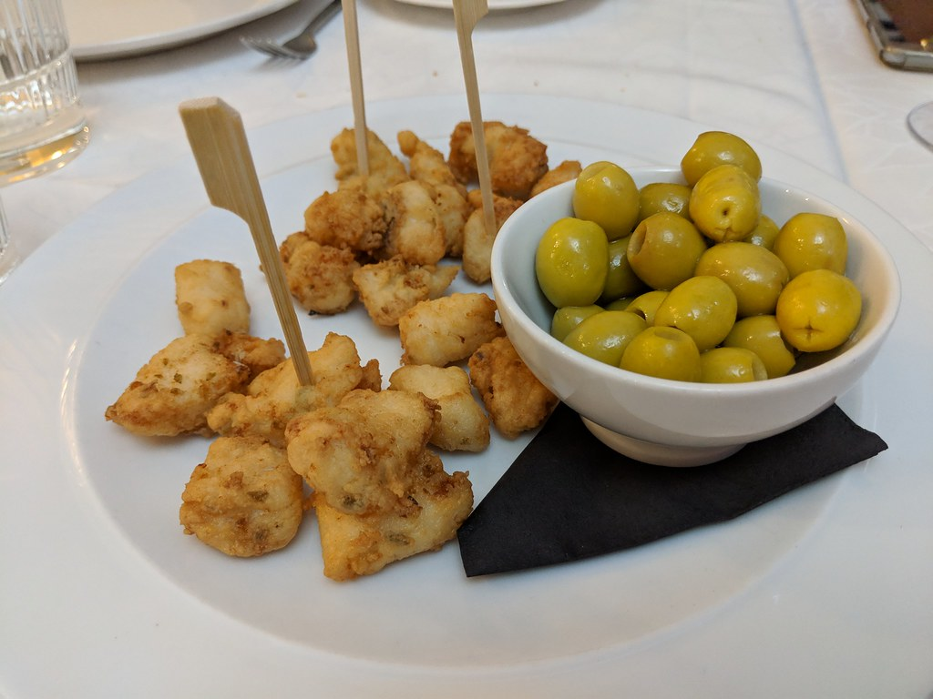 A plate of cazon - local fried dogfish next to a bowl of green olives