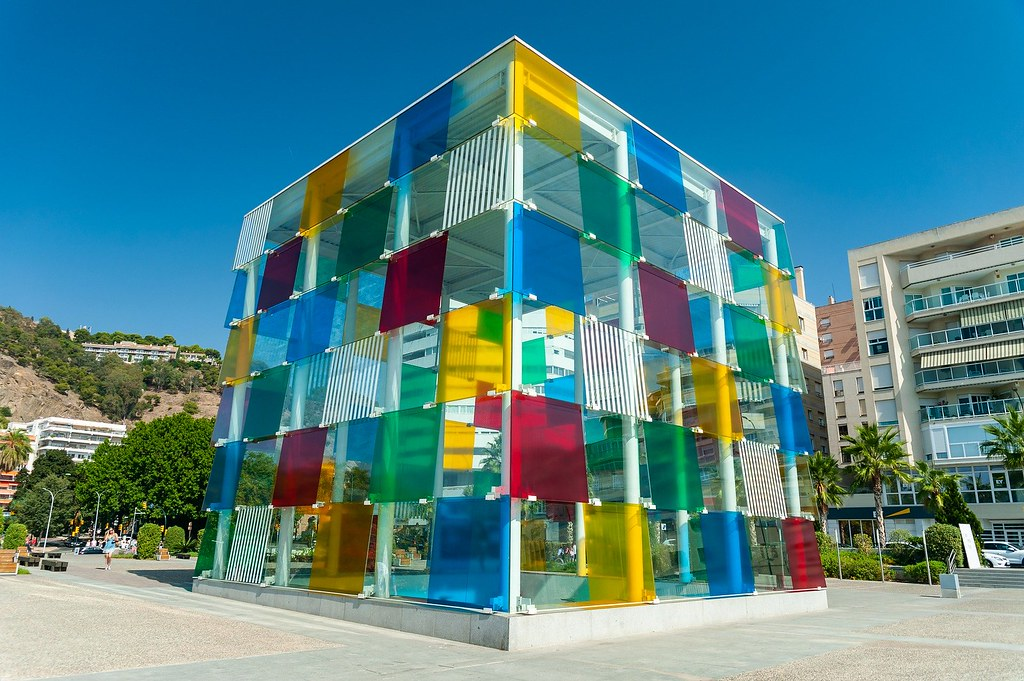 The colorful cube at the entrance of Centre Pompidou. It is a few meters high and has red, yellow, blue and green smaller see through cubes on it which reflect the light.