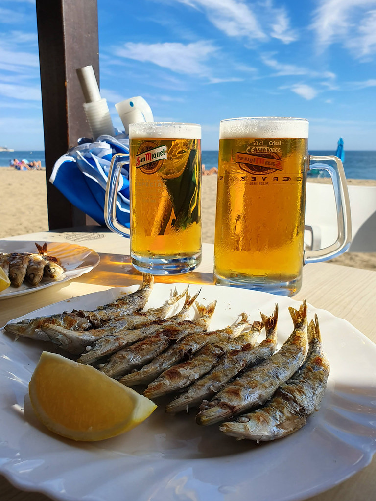 A plate of grilled sardines next to two pints of golden beer. Behind you can see the beach and the sea, and the blue sky.