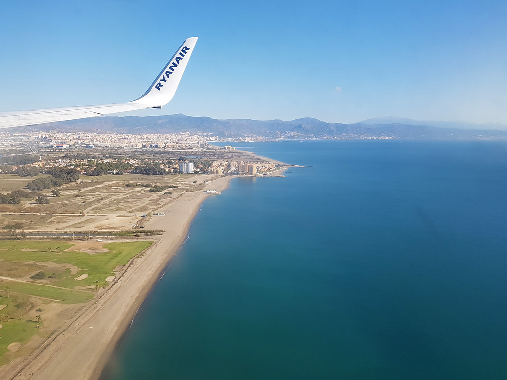 A view from the plane as landing to Malaga airport. The sea below is a beautiful shade of azure blue, next to the golden colored wide beaches. In the back of the photo you can notice the city of Malaga
