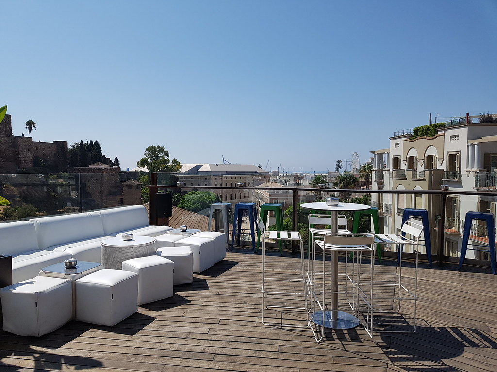 The terrace from Alcazaba Hostel, with white sofas and a view over the old buildings in town