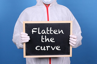 Doctor in protective clothing showing blackboard with Flatten the Curve message | by focusonmore.com