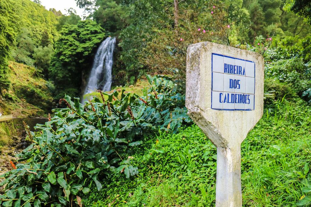 Letrero de Ribeira dos Caldeirões situado delante de la cascada principal situada a un lado de la carretera