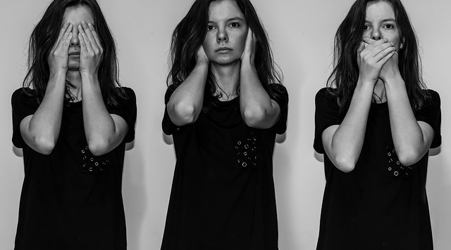 A black and white photo illustration of a young Caucasian woman in three poses: 'see no evil, hear no evil, speak no evil'