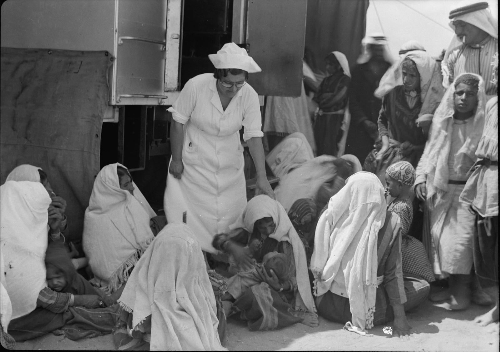Одна из медсестер возле фургона среди женщин и детей деревни