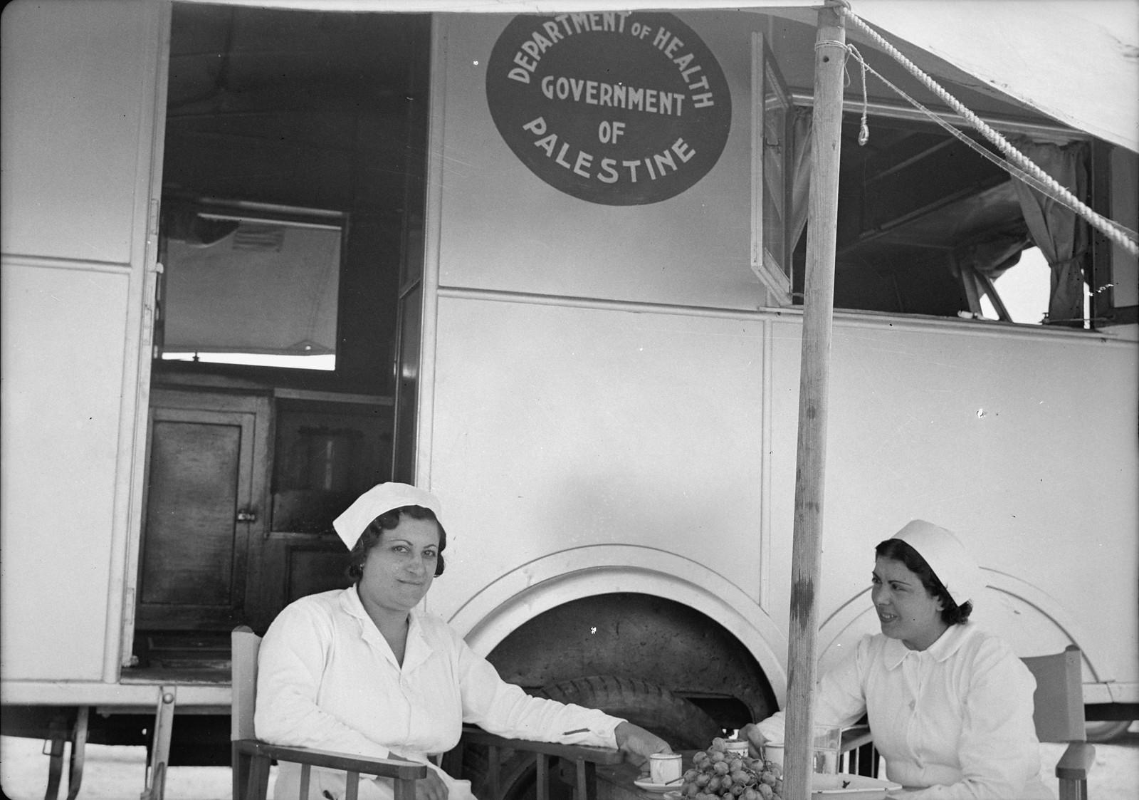 Две медсестры пьют чай рядом со своим спальным фургоном