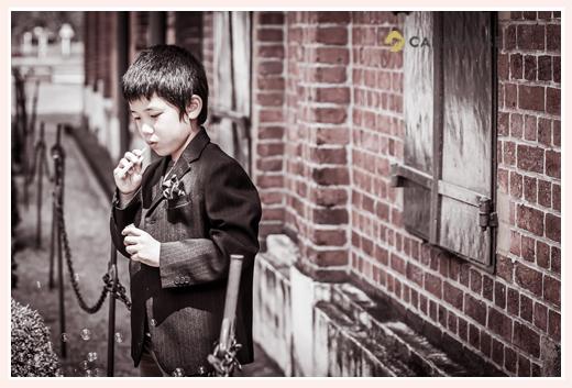 レンガの建物の前で決めポーズの男の子 正装