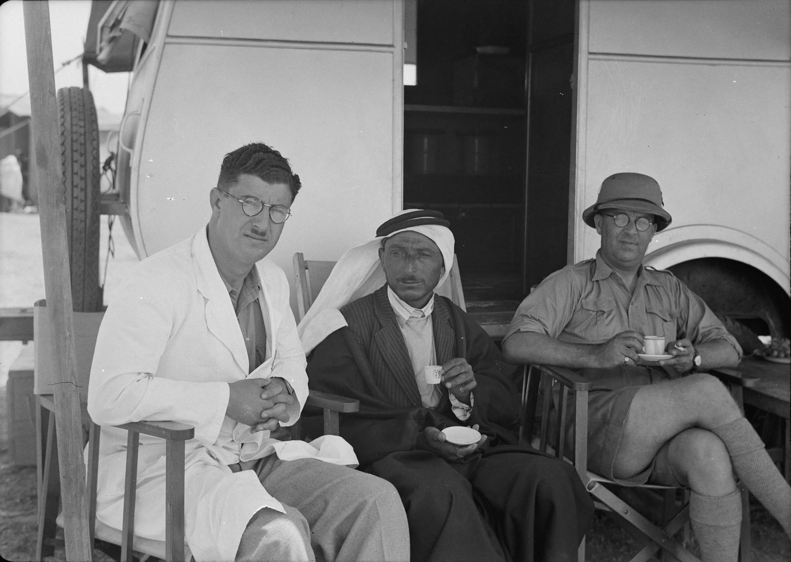 Доктор Шукер, мухтар села Неджд и доктор В.Л. Фергюсон пьют кофе в тени фургона