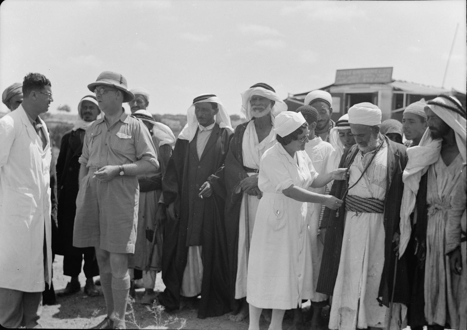 Группа арабов из окрестных деревеннь общается с врачами и медсестрами