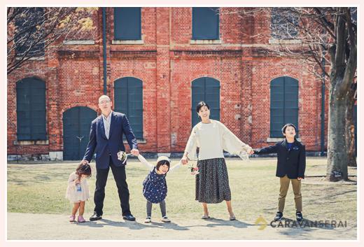 レンガ造りの建物の前で家族写真