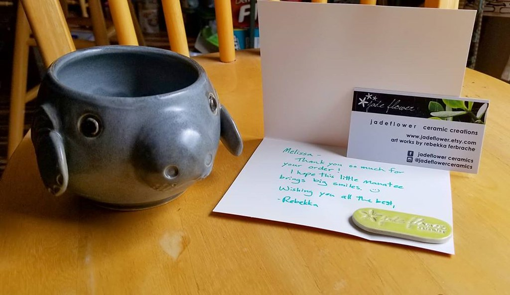 A manatee pottery mug/pot with a card from Jade Flower Ceramics