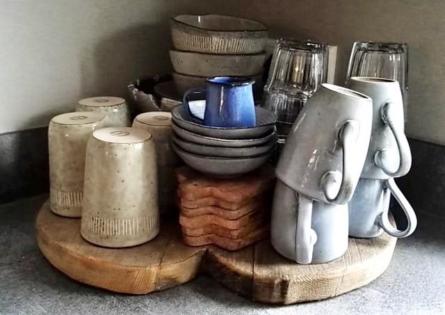 Kopjes en glazen op houten plank hoekje aanrecht