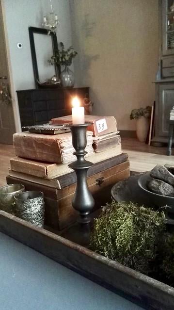 Dienblad met oude boeken en kaars op salontafel