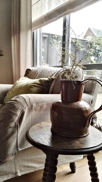 Landelijke fauteuil met hoes tafeltje met koperen pot