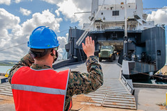 Marine Lance Cpl. Jacob Blanton directs movement of a truck during an operation to offload equipment for an expeditionary medical facility from USNS Dahl (T-AKR-312). (U.S. Navy/MC1 Nathan Carpenter)