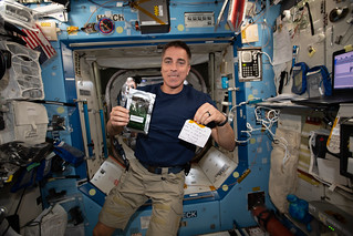 Astronaut Chris Cassidy holds a Parmigiana di Melanzane meal packet