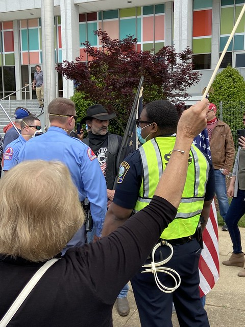 REOPEN NC RALLY DOWNTOWN RALEIGH NC 4 21 2020.  Police speak with shotgun toting protester.