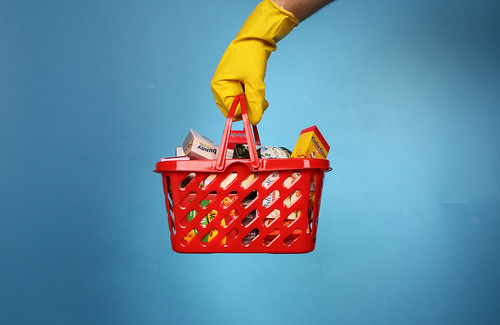 'Follow Shopping basket and hand in a rubber glove isolated on blue background. Safe shopping concept.' by Jernej Furman