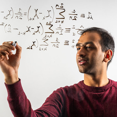 Economics student drawing equations on a board
