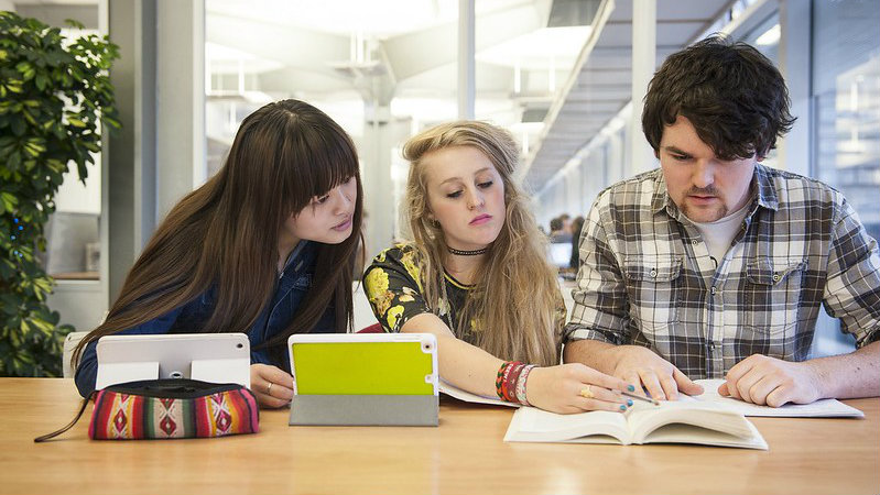 Two female and one male student sat in front of two propped up IPads referring to an open text book.