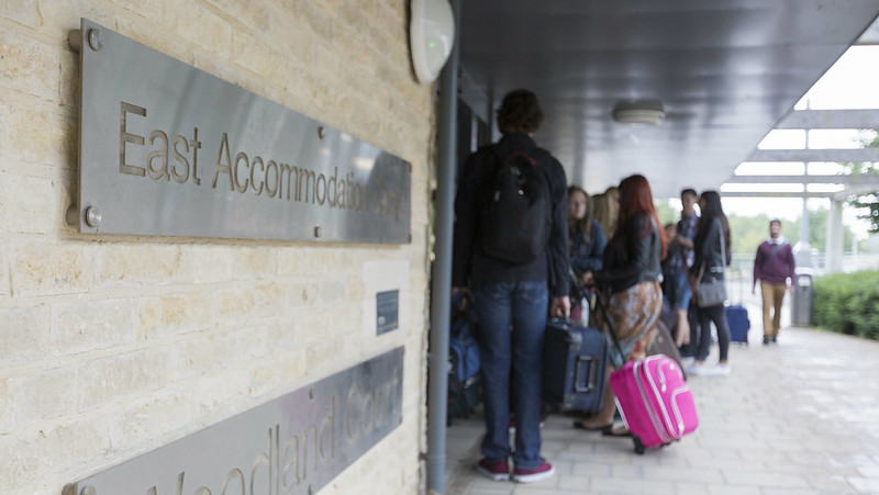 Students with suitcases going into campus accommodation. Two silver-coloured wall plaques says 'East Accommodation' and 'Woodland Court'