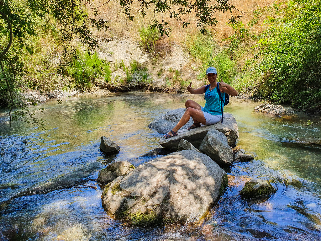 I am sitting down on a large rock, in the river, showing thumbs up towards the camera. I am wearing white shorts, a green tank top and a white cap