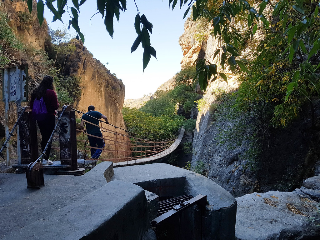 Two people starting to cross the 55 meters long hanging bridge. The bridge has red metal bars that protect you from falling, and wooden steps. The bridge hangs between two rock walls.