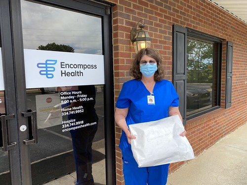Health care worker holding a package.
