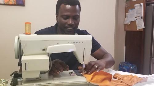 Joseph Emmanuel Quansah sewing a mask.