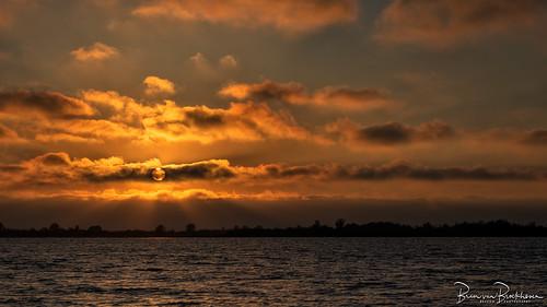 Sun behind a cloud at sunset