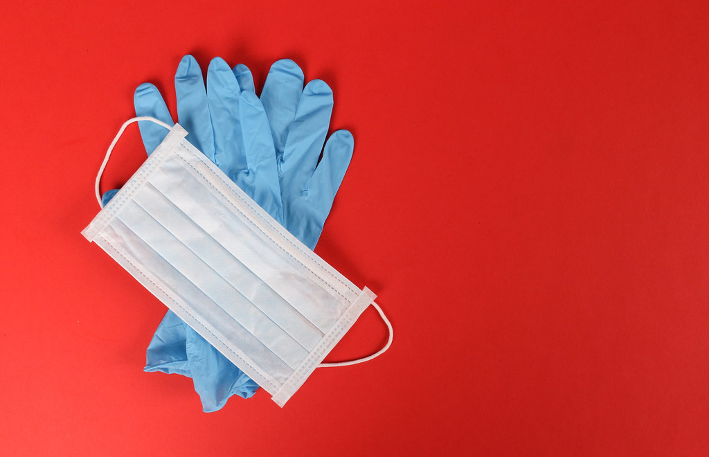 Protective gloves with a face mask on red background