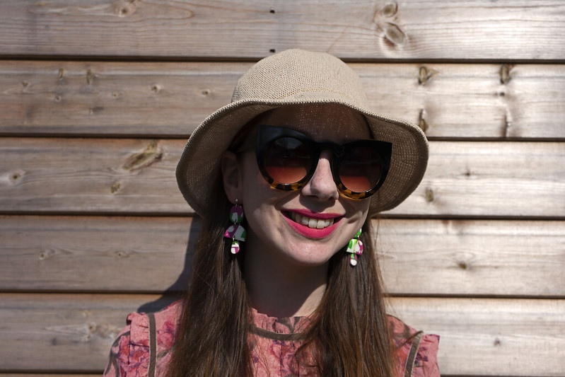 Pink dress a summer hat and statement earrings