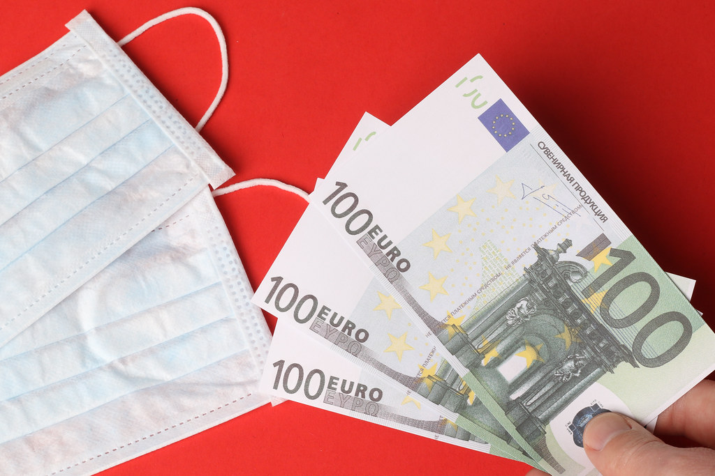 Protective face masks with 100 Euro banknotes on red background
