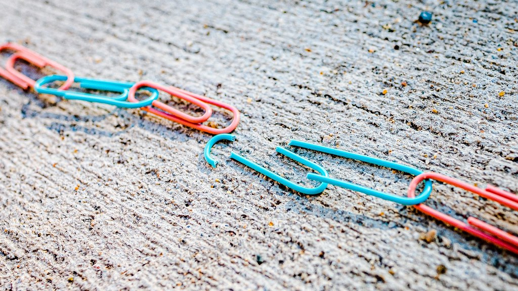 Paper clips attached to one another but separated in the middle, a broken chain