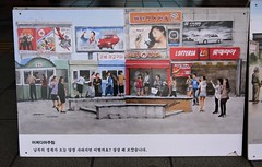 "Seoul Korea 2020 outdoor art exhibit at Seoul Station Plaza showing North and South Korea streetscapes - ""Two Koreas"""