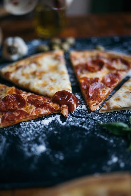 Closeup of ketchun on pizza.