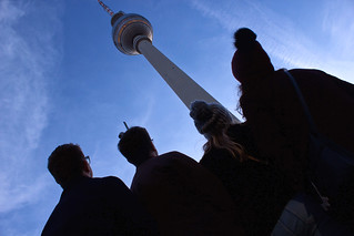 back of a group of 4 students looking up to Berlin tower