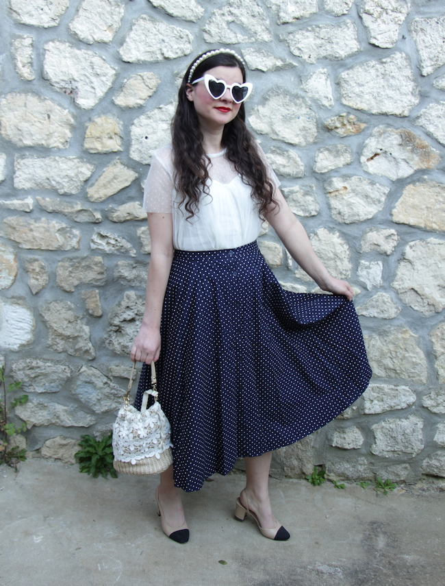 Look top blanc, jupe midi marine à pois et escarpins bicolores façon Chanel