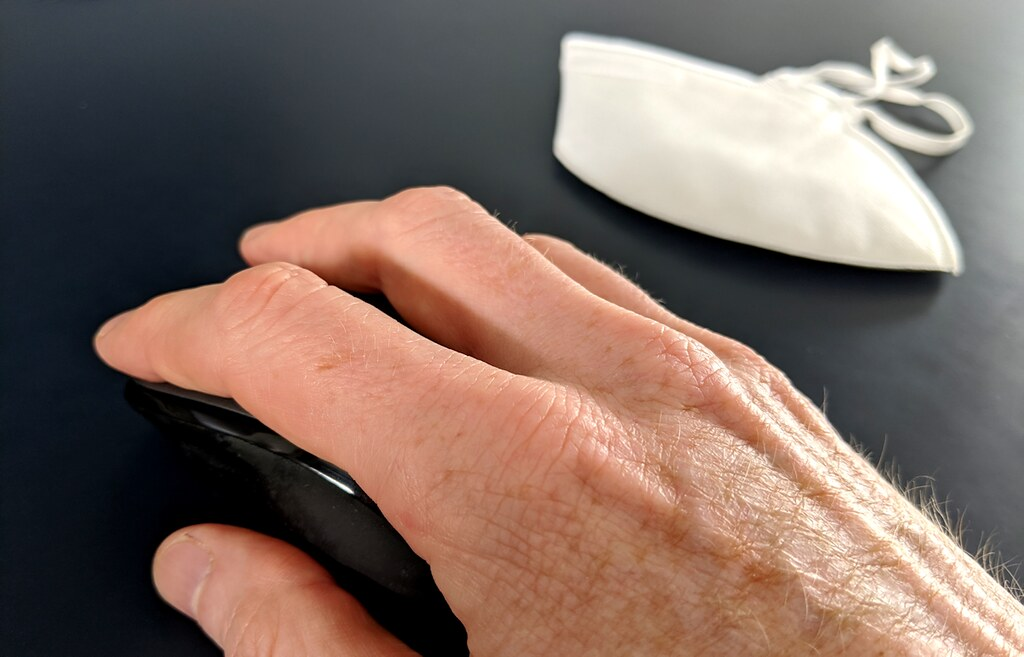 A hand on a computer mouse, with a face mask in the background.