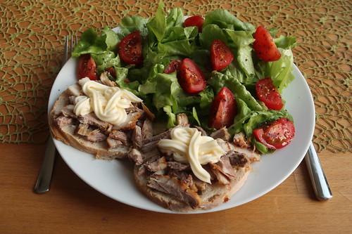 Pulled Lamb Ribs mit Mayonnaise auf Weißbrotrest zu grünem Salat mit Tomatenachteln