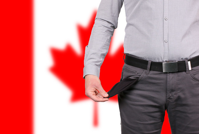 Businessman showing empty pockets over flag of Canada