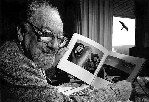 Nicolás Muller viendo un libro con fotografías suyas