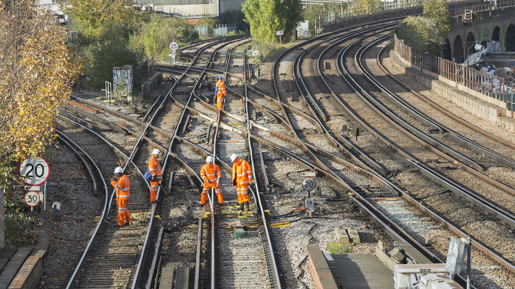 Workers wearing high-vis jackets inspect railway lines.