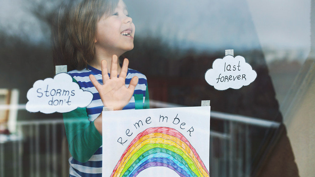 Boy at window during lockdown with a rainbow drawing.