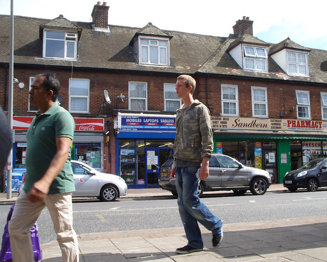 PEOPLE WALKING ON THE SIDEWALK OR PAVEMENT  SHOPPING STREET WITH STORES AND AUTOMOBILES OR MOTOR CARS ON AN EAST LONDON STREET ENGLAND SS855584