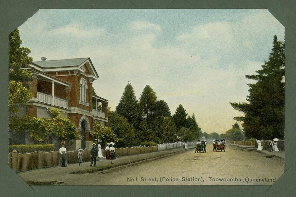 Two cars passing on Neil Street, Toowoomba in front of the police station